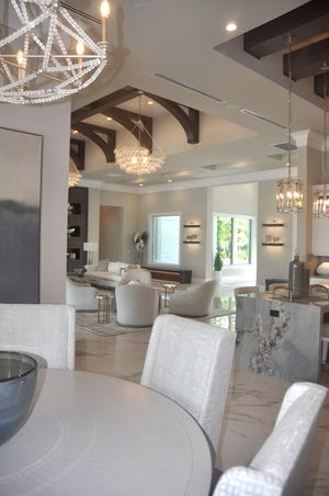 Thick wood beams attached in a barrel shape over a white shiplap ceiling give both elegance and warmth to the room. The same type of beams form a crisscross pattern over the white shiplap ceiling in the nearby kitchen.