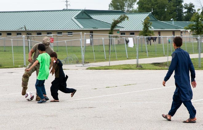 A soldier plays soccer with children at Camp Atterbury, Indiana Saturday, Sept. 4, 2021. The division soldiers, along with members of the Indiana National Guard, are providing temporary housing and support to Afghan evacuees as part of Operation Allies Welcome.