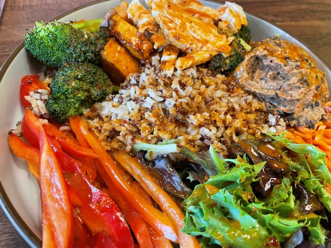 The Happy Hummus Bowl at Redbud Cafe features black-bean hummus, roasted broccoli and sweet potatoes, a quinoa blend, carrots, red bell peppers, petite greens and sweet chili vinaigrette.