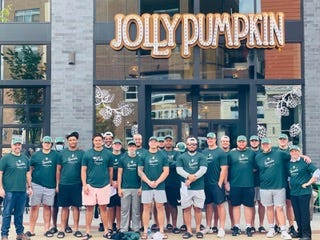 MSU's offensive linemen and long snappers pose outside Jolly Pumpkin in East Lansing, their new endorsement opportunity.