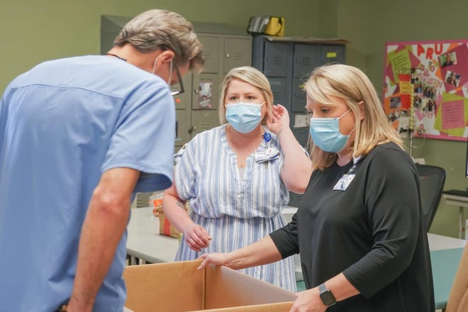 Sonyia Gower delivers food to a doctor at Baxter Regional Medical. Gower took charge of food delivers after members of the community flooded the hospital with donations.