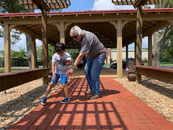 A veteran shows his grandson commemorative bricks on the Town of Pike Road Veterans Memorial Walk of Honor. September 17 is the deadline to order commemorative bricks for this November's installation ceremony.