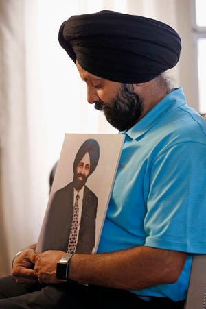 """In this Aug. 19, 2016, photo, Rana Singh Sodhi holds a photograph of his murdered brother, Balbir Singh Sodhi, in Gilbert. The Sikh American was killed at his Arizona gas station four days following the Sept. 11 attacks by a man who announced he was """"going to go out and shoot some towel-heads"""" and mistook him for an Arab Muslim."""