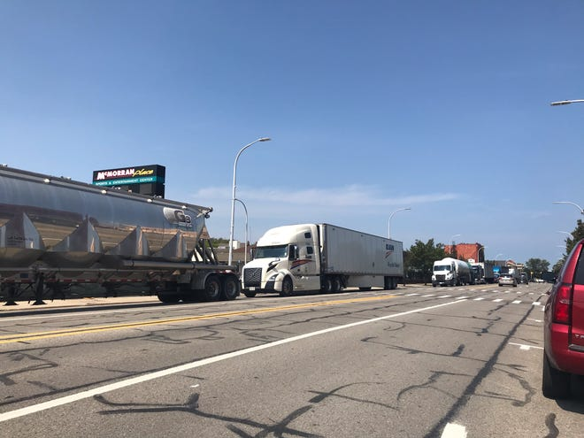 Semi trucks drive through downtown Tuesday, Sept. 7, 2021.