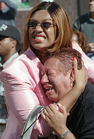 Two women hold each other as they watch the World Trade Center burn following a terrorist attack on the twin skyscrapers in New York Tuesday, Sept. 11, 2001. Terrorists crashed two planes into the World Trade Center and the twin 110-story towers collapsed Tuesday morning.