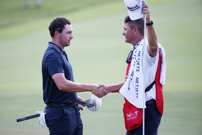 Patrick Cantlay celebrates with caddie Matt Minister on the 18th green after winning during the final round of the TOUR Championship at East Lake Golf Club on Sept. 05, 2021 in Atlanta.