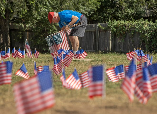 Tony Thompson of the Northwest Austin Rotary Club helps set up 300 miniature American flags at Balcones Country Club on Wednesday to honor the victims of the Sept. 11, 2001, terrorist attacks. The Rotary Club will host a public ceremony at the country club at 9 a.m. Saturday to commemorate the event's 20th anniversary.