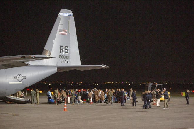 In this Aug. 29 photo families evacuated from Kabul, Afghanistan, walk past a U.S Air Force plane that they arrived on at Kosovo's capital Pristina International Airport. [AP PHOTO/VISAR KRYEZIU/FILE]