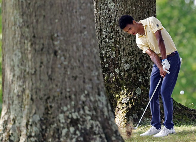 Hoban's Solomon Petrie hits his ball from the tree line off of the No. 9 fairway at Portage Country Club, Tuesday, Sept. 7, 2021, in Akron, Ohio.
