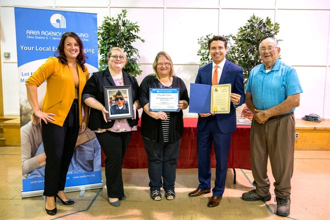 At a ceremony to posthumously honor Kirby Nesbitt are from left, Nicole Williams, vice president of outreach and development for Ohio District 5 Area Agency on Aging; Plymouth Mayor Cassaundra Fryman, holding a photograph of Kirby Nesbitt; Terry McQuillen, who nominated Nesbitt; Ashland Mayor Matt Miller, and Thomas Kranz, 2017 Outstanding Senior Citizen.