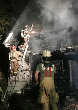 Firefighters from three departments work to cut an access hole in the front of a burning Stapleton home Sunday, Sept. 5, so they can use hoses to douse flames in the structure's roof.