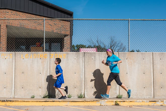 Jeannine Lee, pre-K teacher at Jane Phillips Elementary, runs to support fifth-grade students as part of the Bruins on the Run program.