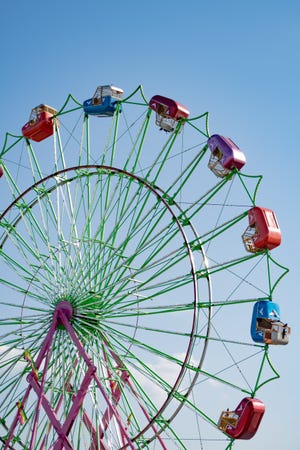 A Ferris wheel sits against a late summer sky as it awaits passengers at the Belmont County fair.