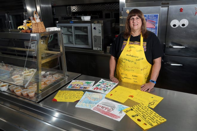 Jill Martie, head cook at Taylor Road Elementary, retired Sept. 1 after working with Reynoldsburg City Schools for 27 years. She is shown inside the school cafeteria with cards made by students and wearing one of the four aprons signed by students and faculty she received on her last day.