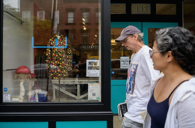 """A couple walks past a """"now hiring"""" sign posted at a store in New York City on August 20, 2021. The number of available job openings rose to 10.9 million during July. (Angela Weiss/AFP/Getty Images/TNS)"""