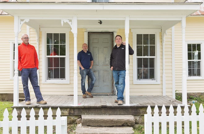 From left, Aaron Heydinger, Nate Hatfield and Garrett Gandee in front of the Cross House, one of the homes they are restoring in Kilbourne.