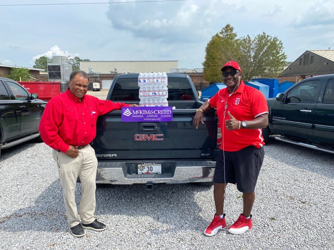 """Donaldsonville Mayor Leroy Sullivan and Ascension Parish Councilman Alvin """"Coach"""" Thomas coordinated with McKim and Creed (formerly Glenn Shaheen and Associates) a donation of water for the Donaldsonville High School football team."""