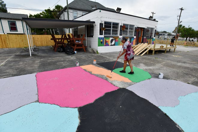 Cherron Johnson adds a little color to brighten the aged concrete of what will become a part of the outdoor dining area at Main Street Food Park in Jacksonville. Johnson and her husband are transforming the site with plans to open the food truck park in October in the Springfield community. It will be a family-oriented park featuring food trucks, live entertainment and games for children and adults.