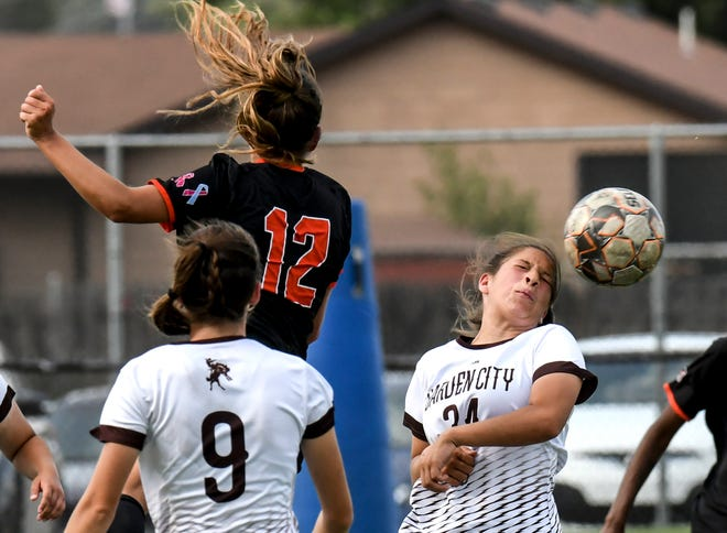 Garden City Community College's Haily Enriquez, right, takes the ball off her head to steal a Cowley County pass Sept. 1 at Broncbuster Stadium.  GCCC routed Neosho County on Sunday, 6-1