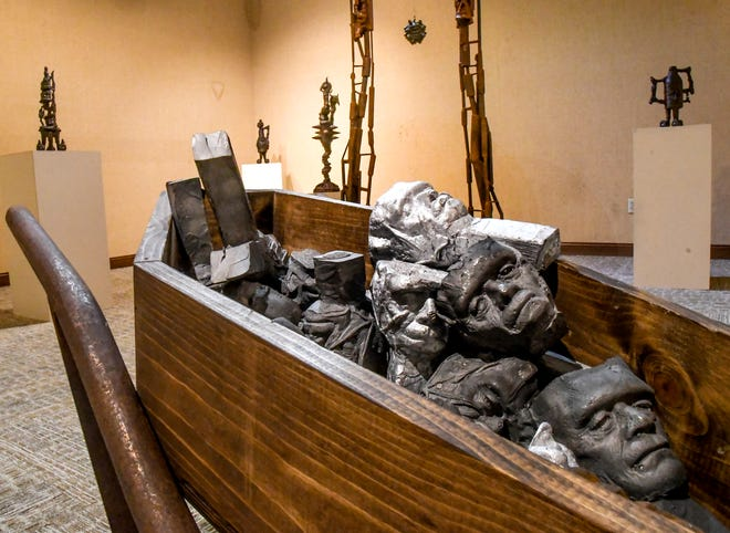 """A wheel barrow filed of aluminum and cast iron Frankenstein pour cups is among the sculptures in an exhibit by Zane Mahanna showing at Garden City Community College's Merecer Gallery. The exhibit, titled """"THUNDERMUSCLE"""", runs through Oct. 1."""