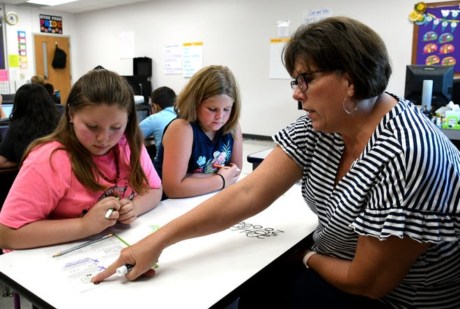 """Hyde Park teacher Robin Petty helps a group of her 4th graders understand and solve complex math problems using her classroom's dry-erase desk. """"It's so good to be back in the classroom with our kids,"""" said Petty. """"I think we've all returned with a renewed energy and dedication to helping our kids learn, grow and thrive academically and personally…to become the best people they can be in all areas of their lives."""