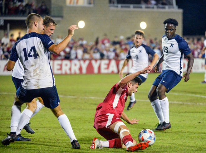 Indiana's Victor Bezerra (7) attempts a sliding tackle to control the ball in the box during Monday's match against Xavier at Bill Armstrong Stadium.
