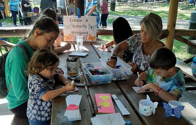 Jillian Ristow and her daughter, Adeline, left, create a souvenir during Art in the Park Sunday, Sept. 5, 2021, in Krape Park in Freeport.