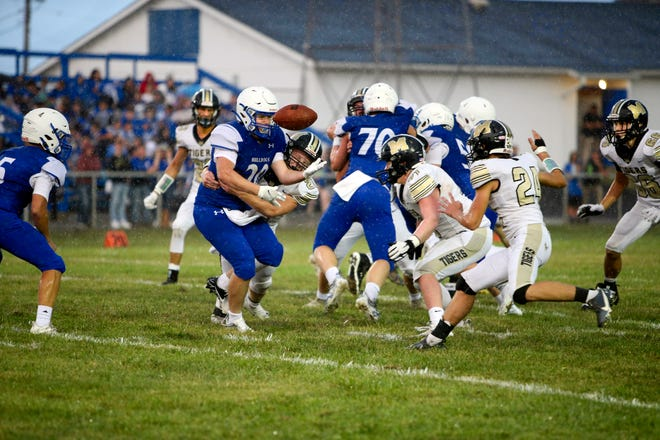 """Quick penetration and a solid hit by Marceline High School football Tigers senior linebacker Hunter Nelson separates Brookfield running back Tommy Gunn from the already-wet ball during the first half of the Friday, Sept. 3, """"Bell Game"""" between the Linn County high schools. Already moving in, anticipating putting their own """"lick"""" on the ballcarrier, but about to adjust to trying to recover the fumble, are MHS'  Ryder Gooch (24) and Nathan Cupp  (71), while Mason Barnett (66) lurks nearby. Virtually the entire first half of the rivalry game was played in rain – at times very heavy, before the clouds closed up after halftime and Marceline scored all 2- of the game's points following intermission to recapture possession of the prize bell."""