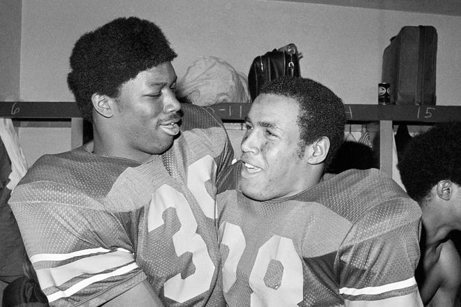 In this Jan. 1, 1973, file photo, Southern California fullback Sam Cunningham, left, and running back Anthony Davis embrace after USC's 42-17 triumph in the Rose Bowl against Ohio State in Pasadena, Calif. Cunningham died Tuesday, Sept. 7, 2021, at his home in Inglewood, Calif., according to USC. He was 71.