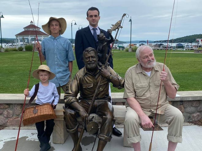 Actors portraying Hemingway at different points in his life pose with the new Hemingway statue in Walloon Lake.