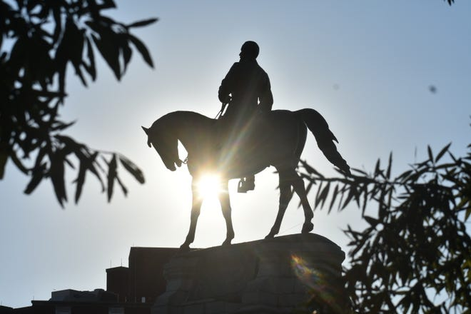 The statue of Confederate Gen. Robert E. Lee is silhouetted against the setting sun on Monument Avenue  in Richmond Tuesday, Sept. 7, 2021.
