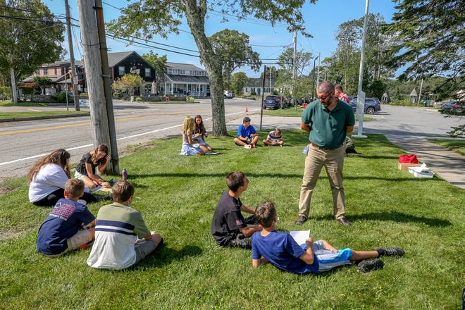 Teacher Michael Tomasso leads eighth-graders in a class outdoors on their first day back Wednesday at Wilbur & McMahon School in Little Compton. Last year, the school held classes in tents when it was cold and on the front lawn when it was mild.