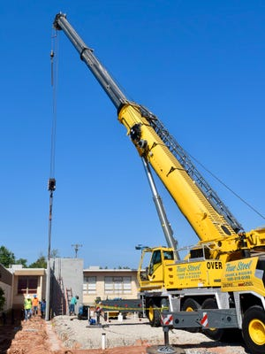 A crane moves large concrete panels for the new Will Rogers Elementary School safe room.