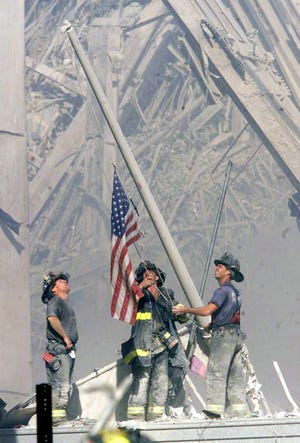 Firemen raise a United States flag on Sept. 11, 2001, where the World Trade Center formerly stood. Today is the 20th anniversary of the terrorist attacks.