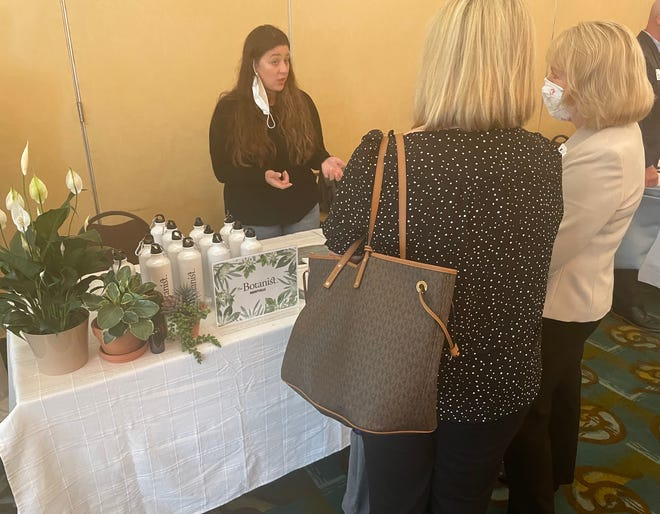 """Sierra Lloyd, a patient care coordinator for The Botanist in Uncasville, explains the company to guests at the Chamber of Commerce of Eastern Connecticut's """"The Business of Cannabis"""" Mini Expo Wednesday."""