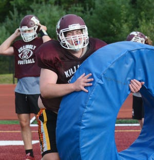 Killingly High School's Shane LeDuc works with a tackling ring during practice in Dayville. At left, is quarterback Thomas Dreibholz.