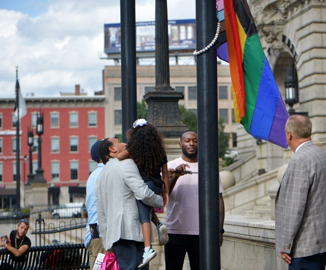 City Councilors Sean Rose and Khrystian King, daughter Leiyani King, 4, stood beside Al Green, ministry director LGBT Asylum Task Force, as Green raised the Pride flag Wednesday with Mayor Joe Petty at right.