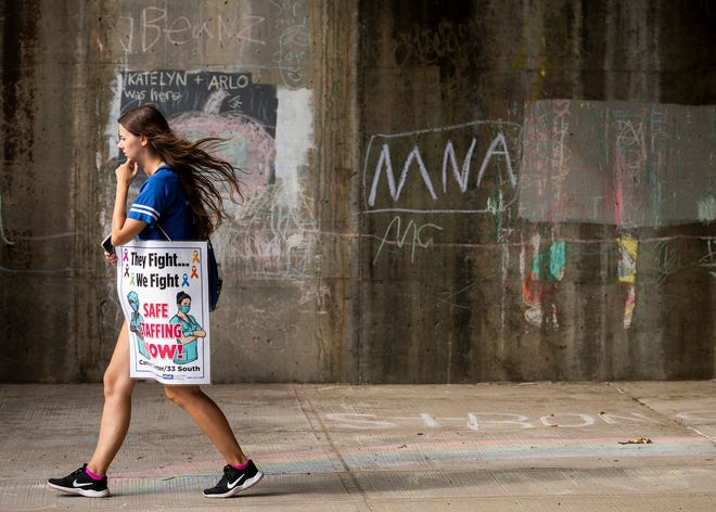 Nurse Brianna Young walks past sidewalk chalk that reads 'MNA Strong' on the six-month anniversary of the start of the St. Vincent nurses strike on Wednesday.