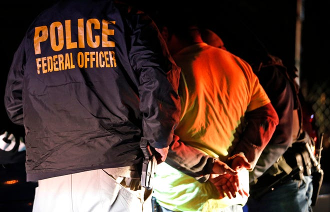 U.S. Immigration and Customs Enforcement agents detain a person during a raid.