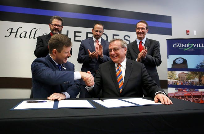 Gainesville Mayor Lauren Poe, left, shakes hands with UF President Kent Fuchs after they signed a partnership between the city and UF during the 2017 State of the City Address held at the Hall of Heroes in the Gainesville Police Department in 2017.