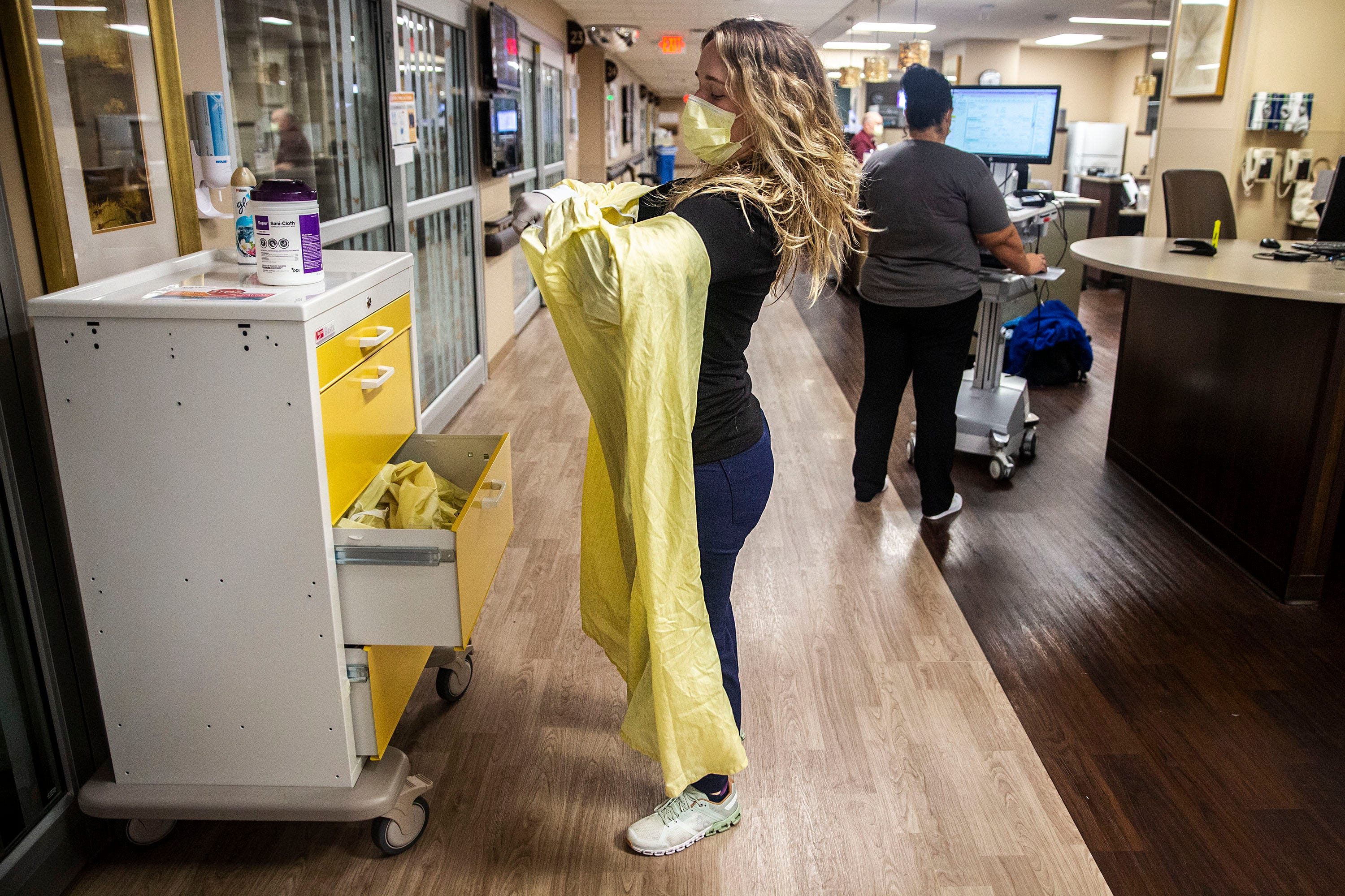 Stephanie Biggins, a registered nurse in the Iowa Methodist Medical Center emergency department, pulls on gown, gloves and a second mask with eye protection, before aiding a patient, early Friday morning, Sep. 3, 2021, in Des Moines.