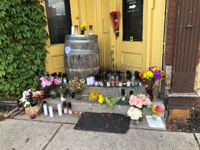 A memorial honoring Greg Mudge, who died on Sunday, is outside his beloved Mudgie's Deli and Wine Shop in Corktown.