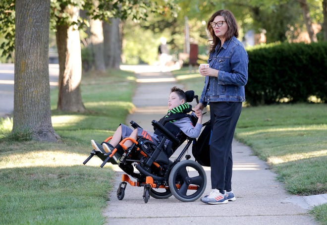 Christine McGovern and her 10-year-old son Jasper wait for Jasper's school bus outside their home in Milwaukee on Wednesday. The bus had not come to pick up Jasper since school began last week.