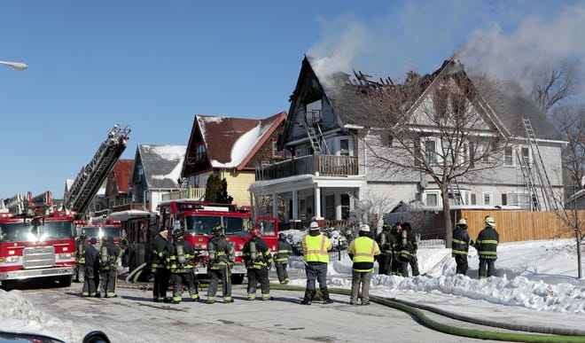 Milwaukee firefighters extinguish a fire Feb. 7 near the corner of West Lloyd and North 17th streets. Milwaukee's yearly pension contribution is scheduled to sharply spike in 2023, cutting into city services unless officials can find a way to head it off.