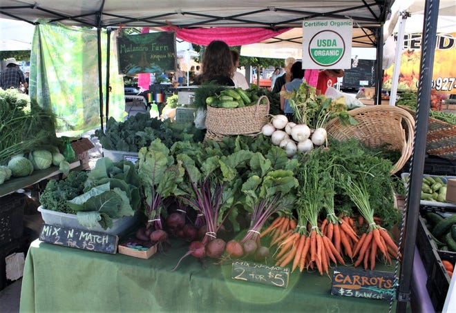 An organic operation sells produce at a farmers' market in New Mexico. The New Mexico Department of Agriculture encourages the organic industry in the state to take advantage of federal funding available to assist with the cost of receiving or maintaining organic certification.