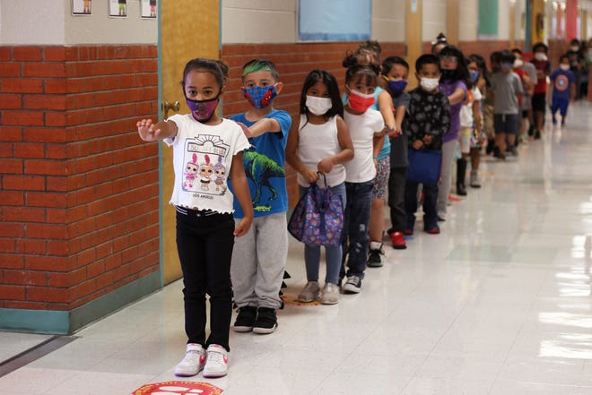 Kindergarten students at Booker T. Washington Community Elementary School line up on their way to lunch on Wednesday, Sept. 8, 2021. They put their arms out straight ahead to help keep social distance between the person in front of them.