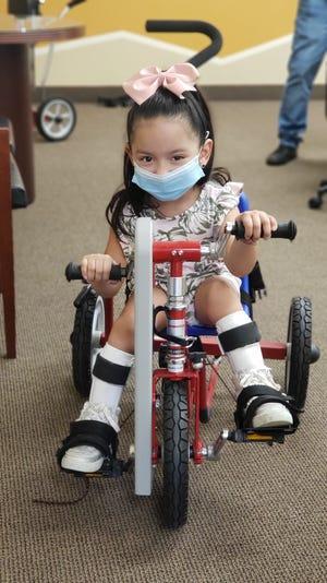 Nenetzy, 4, enjoys her adaptive bike.