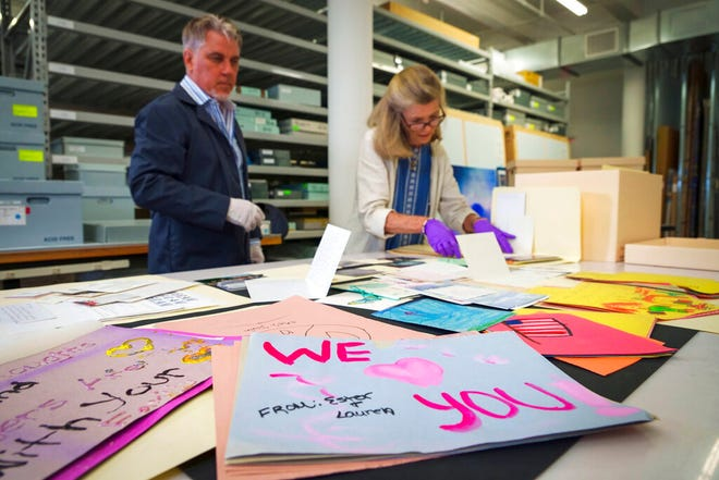 Jan Ramirez, chief curator at the 9/11 Memorial & Museum, right, sifts through a collection of condolence cards for a victim of 9/11 that were donated to the museum's archive, July 16, 2021, in Jersey City, N.J. Over the years, the museum has collected some 22,000 personal artifacts to help tell the stories of those who died and those lucky to survive. Many of those personal effects were plucked from the ruins of what was once the Twin Towers. Other items were donated by survivors or by the families of those who perished.(AP Photo/Robert Bumsted)