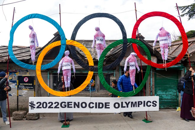 FILE - In this Feb. 3, 2021, file photo, exile Tibetans use the Olympic Rings as a prop as they hold a street protest against the holding of 2022 Winter Olympics in Beijing in Dharmsala, India. Some of the world's largest broadcasters including American network NBC are being asked to cancel plans to cover the 2022 Winter Olympics in Beijing over alleged human rights abuses in the country. The Games open on Feb. 4. (AP Photo/Ashwini Bhatia, File)