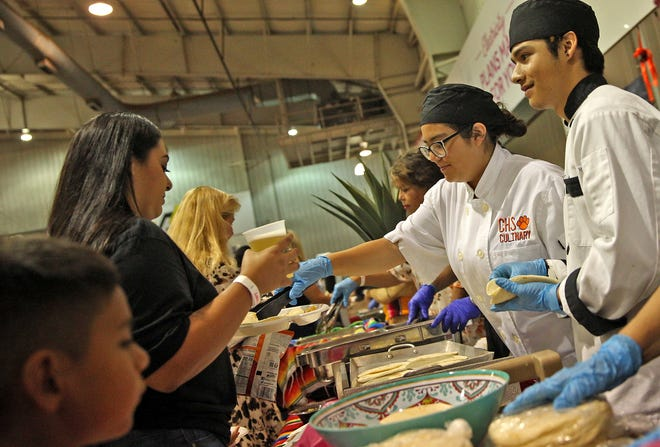 Members of the Central High School Culinary Program, at right, serve food to customers during the Taste of San Angelo event at the Spur Arena on Tuesday, Sept. 7, 2021.